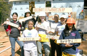 A group of student volunteers from the Hotchkiss School in Connecticut pose with homeowner Yolanda Ferguson during construction on a Habitat for Humanity house in Pickens. Rocky Nimmons/Courier