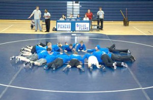 Russell Brinson/Photo Members of the Pickens High School wrestling team work out on the new mat purchased with money they earned doing odd jobs over the summer.