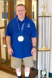 Special to The Courier Easley resident Todd McKinney poses with his recently earned National Special Olympics medals for bowling and a past trophy for softball.