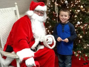 Landen Barrett, 5, the son of Hannah and Matt Barrett of Six Mile, was chosen to light the tree for the town's annual Old Fashion Christmas last Thursday. Pictured at left, Landen sits with Santa after officially lighting the tree to kick off the Christmas season in Six Mile.