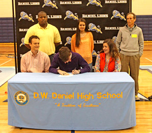 Rex Brown/Courtesy The Journal Joined by family and coaches, Daniel senior Jacob Slann signs with Clemson on Wednesday during a ceremony at the school's gym.