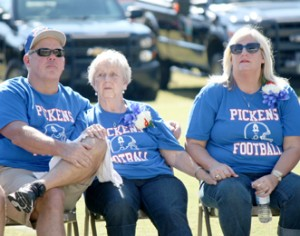 Rocky Nimmons/Courier Bill Isaacs' wife, Peggy, is pictured with their children, Mike and Crystal, during a memorial service held in his honor Saturday at Bruce Field in Pickens.